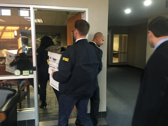 FBI agents carry boxes into Taylor Mayor Rick Sollars' office at City Hall on Tuesday, Feb. 19, 2019.