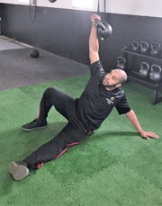 Eugene Barber, owner of Dynamic Baseball Fitness in Elmira Heights, demonstrates an exercise move in his facility.