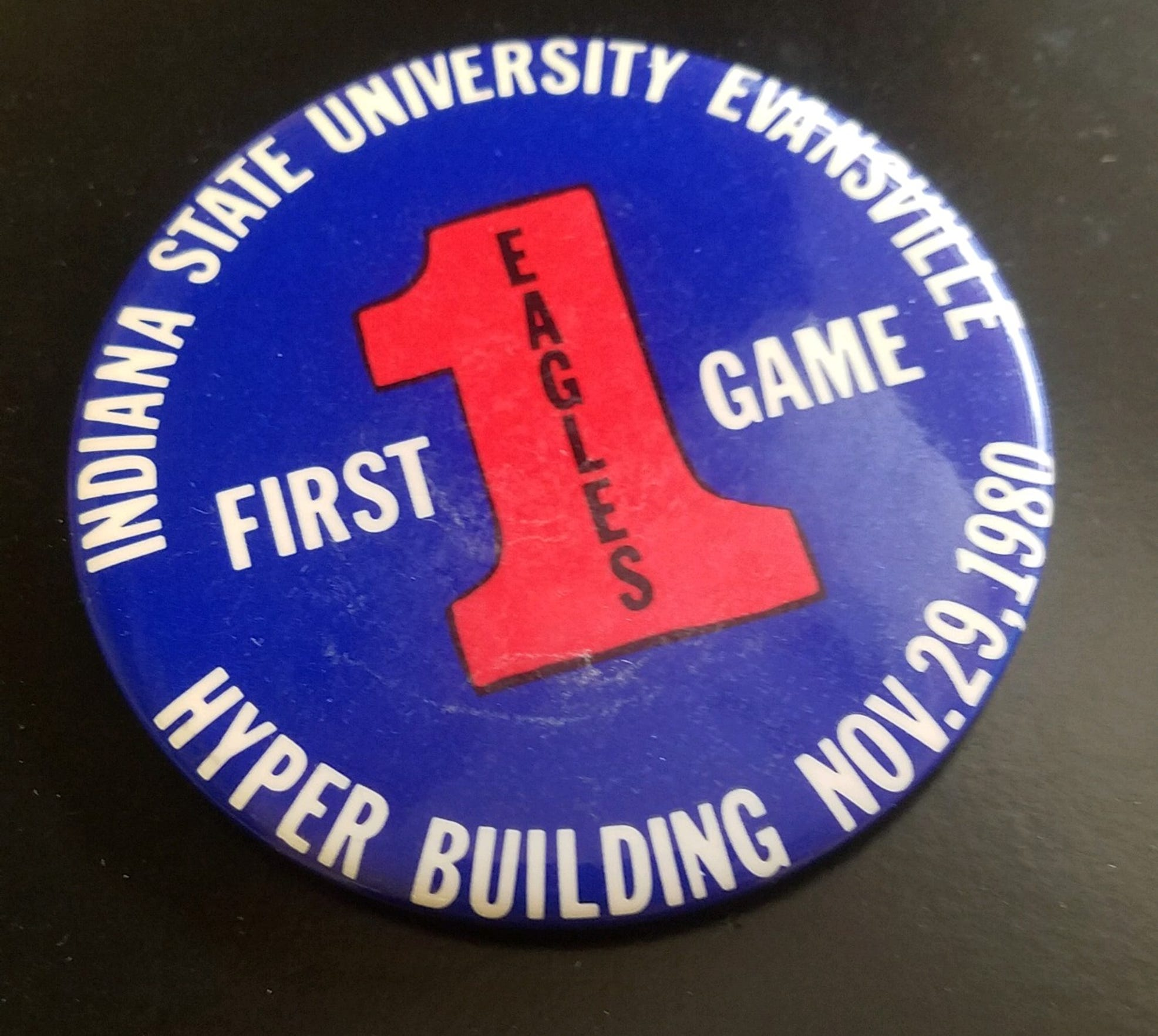 button commemorating the first game played inside the PAC.