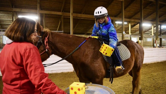 Charlie Hilton, 10, of Port Clinton plays a game on horseback to work on coordination during her December 2018 Riders Unlimited lesson with volunteer leader Sue Hoffman. Riders Unlimited is holding its annual Redneck Plunge and chili cookoff fundraiser Saturday at the organization's Oak Harbor facility, with the cook off starting at 1 p.m. and the plunge taking place at 3 p.m.