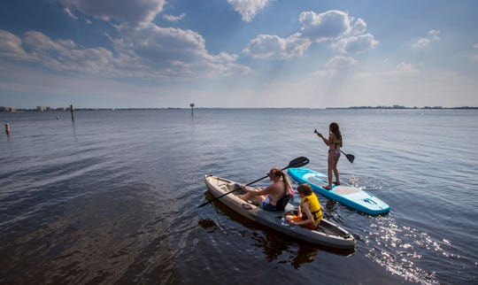 Jennifer Lee, of Cape Coral, and her twin children Baron and Madison Weidenbenner, try out a new kayak and paddleboard during a visit to the Cape Coral Yacht Club Wednesday afternoon.