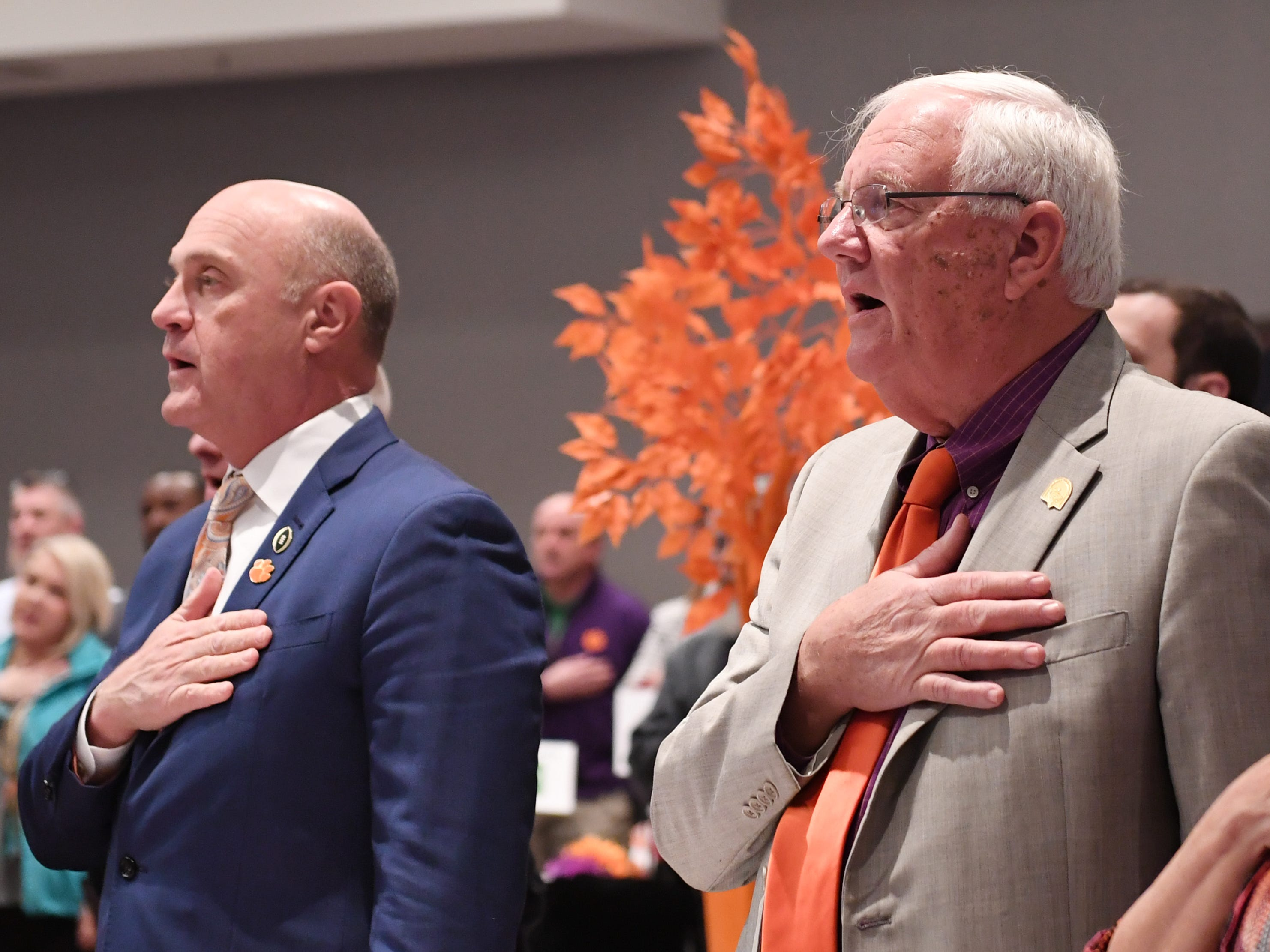 From left, Clemson University President James Clements and City of Clemson Mayor J.C. Cook stand for the Pledge of Allegiance at the start of the State of Clemson event held at the Madren Center Tuesday, Feb. 19, 2019.
