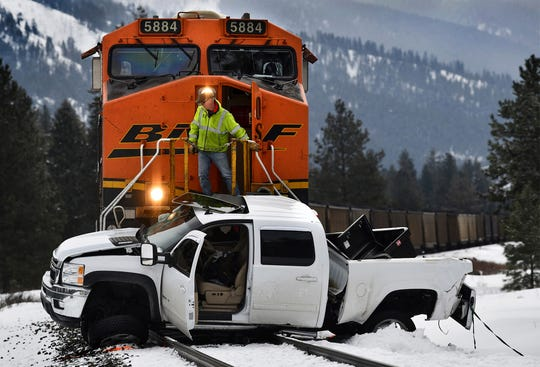 A Montana Rail Link official looks over the scene after a Burlington Northern Sante Fe train collided with a pickup truck at a crossing west of Alberton, Mont., Tuesday, Feb. 19, 2019, injuring the driver of the truck. The truck was pushed about a half a mile down the track before the train could stop. The track is owned by Montana Rail Link. (KurtWilson/The Missoulian via AP)