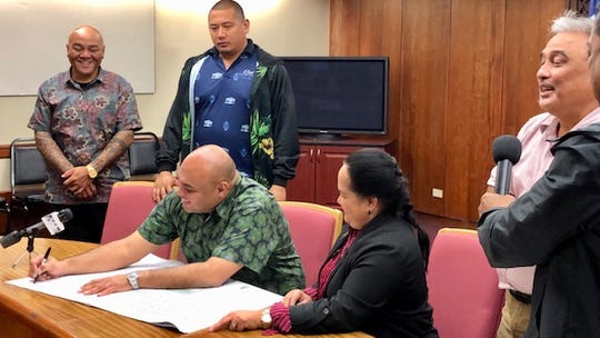 Acting Gov. Josh Tenorio on Tuesday afternoon signs a design plan for one of the new monuments in honor of World War II survivors and victims, to be built ahead of the 75th anniversary of Guam's liberation from the Japanese occupation. Looking on are Speaker Tina Muna Barnes, Agat Mayor Kevin Susuico and Manenggon Memorial Foundation chairman William Flores.