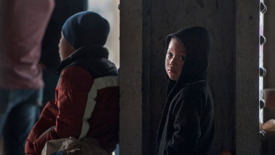 A 5-year-old child tries to stay warm behind a pillar at the Greyhound terminal in Jackson, Miss., on Feb. 19, 2019. He, his father and other migrants from Central America, seeking asylum in the U.S., wait for a bus that will take them on the next leg of a journey as they await for their cases to be heard.