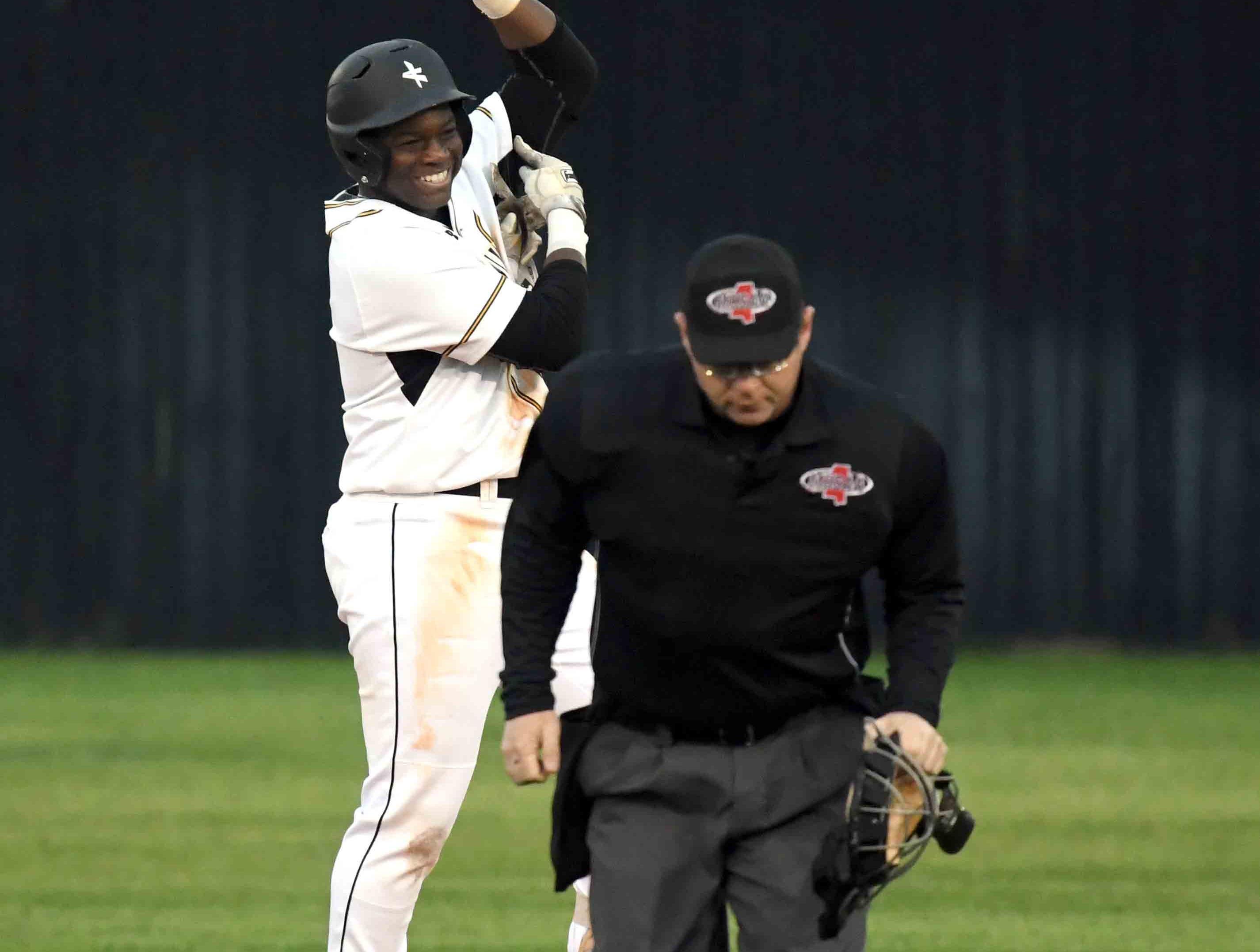 Oak Grove senior Alex Bolling celebrates on second base in their season opener against Seminary in Hattiesburg on Monday, February 18, 2019.