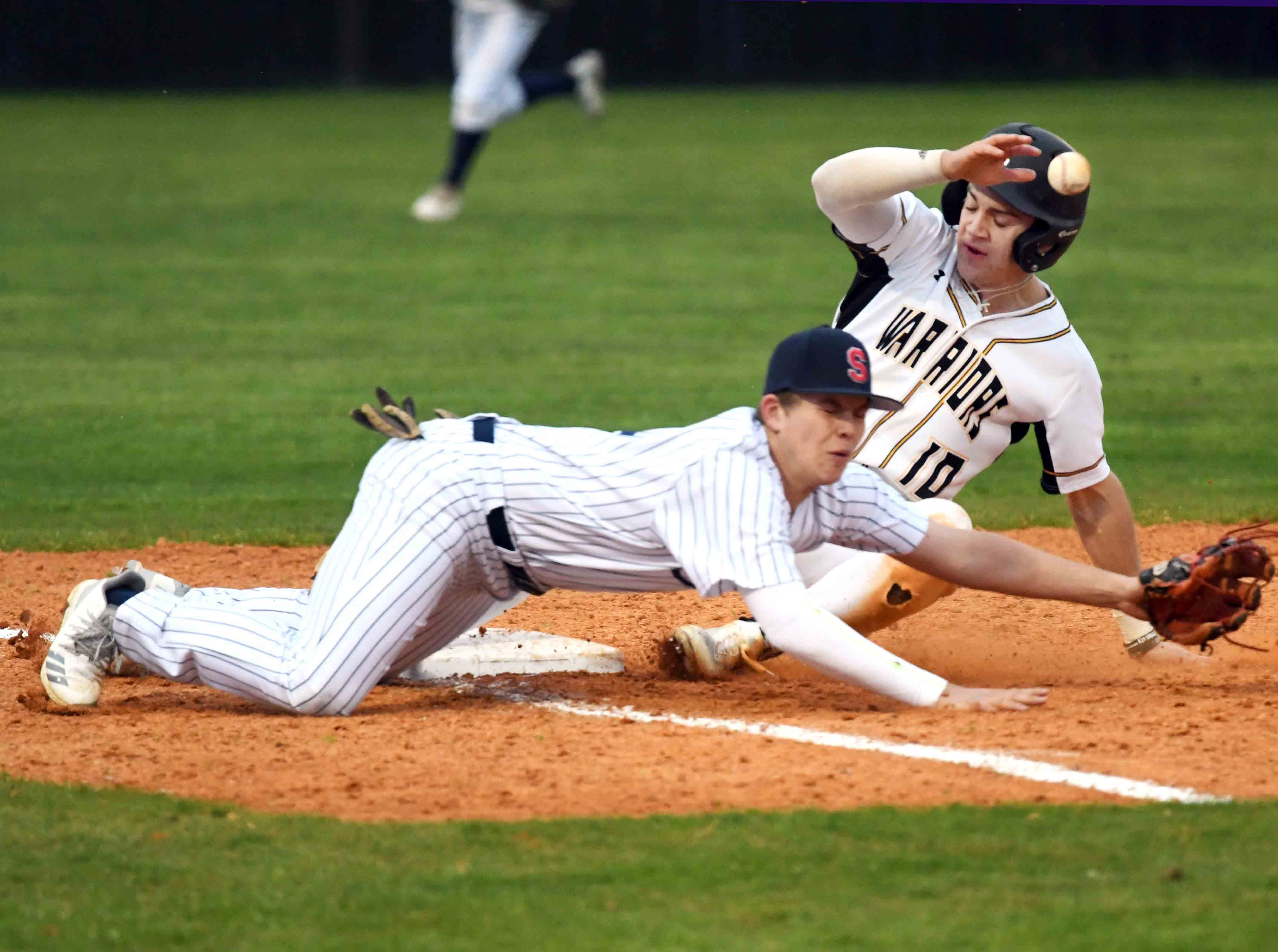 Oak Grove senior John Rhys Plumlee slides into third base  in their season opener against Seminary in Hattiesburg on Monday, February 18, 2019.