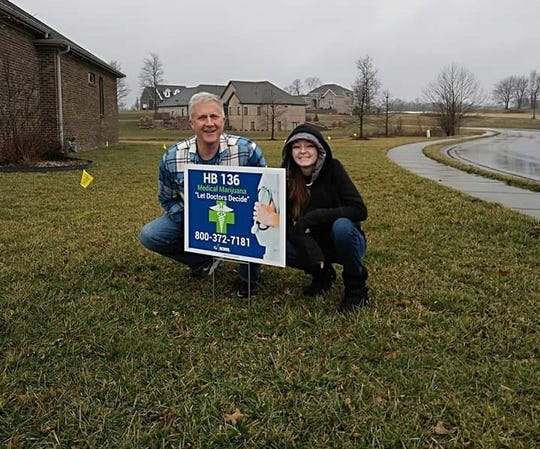 "Kentucky Rep. Rob Wiederstein and Kenzee Myers pose together in the rain after placing a support HB 136 sign in his yard. The sign says, ""Let Doctors Decide"""