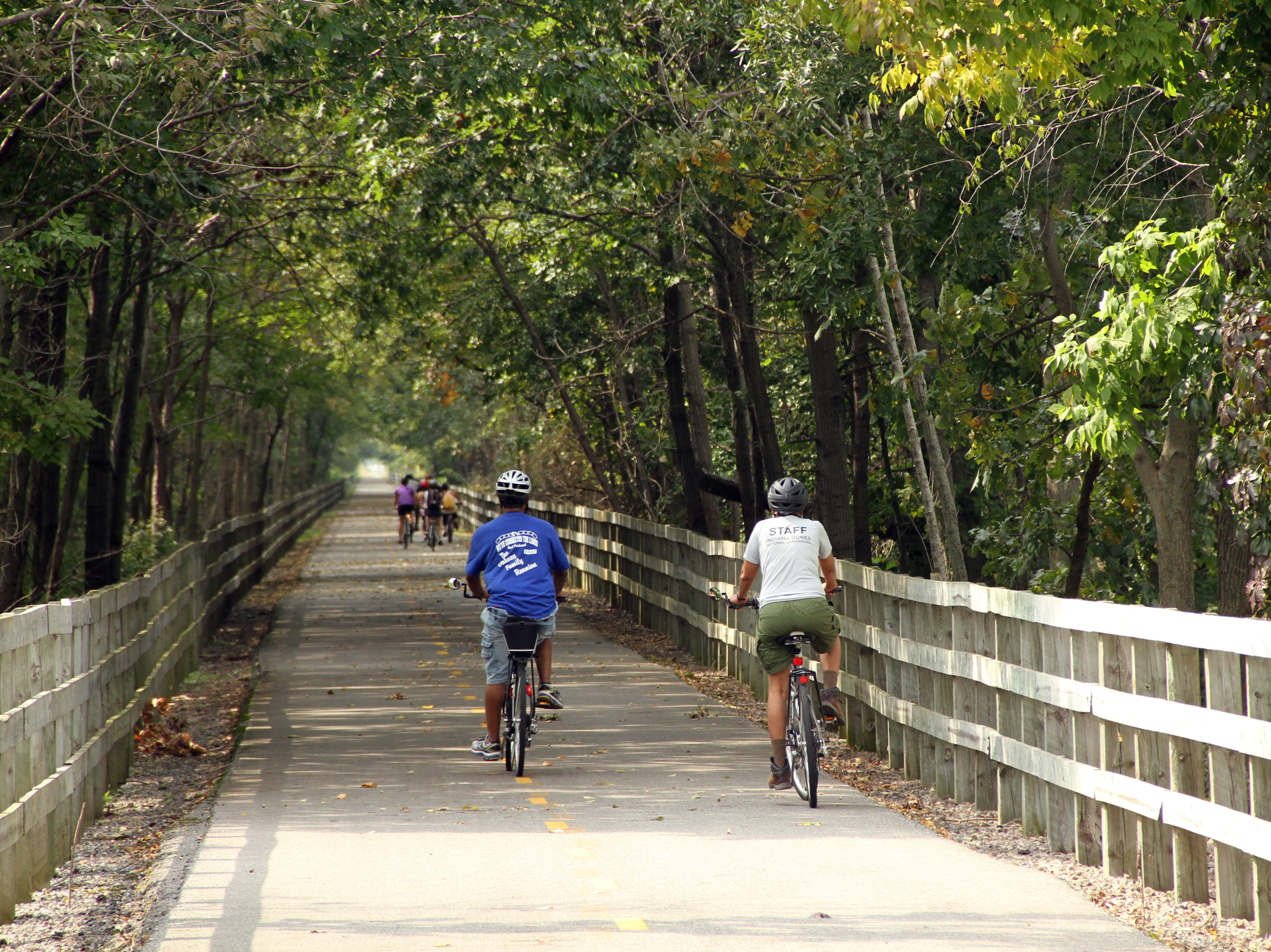 Bicyclists ride on the Oak Savannah paved rail trail at Indiana Dunes National Park.