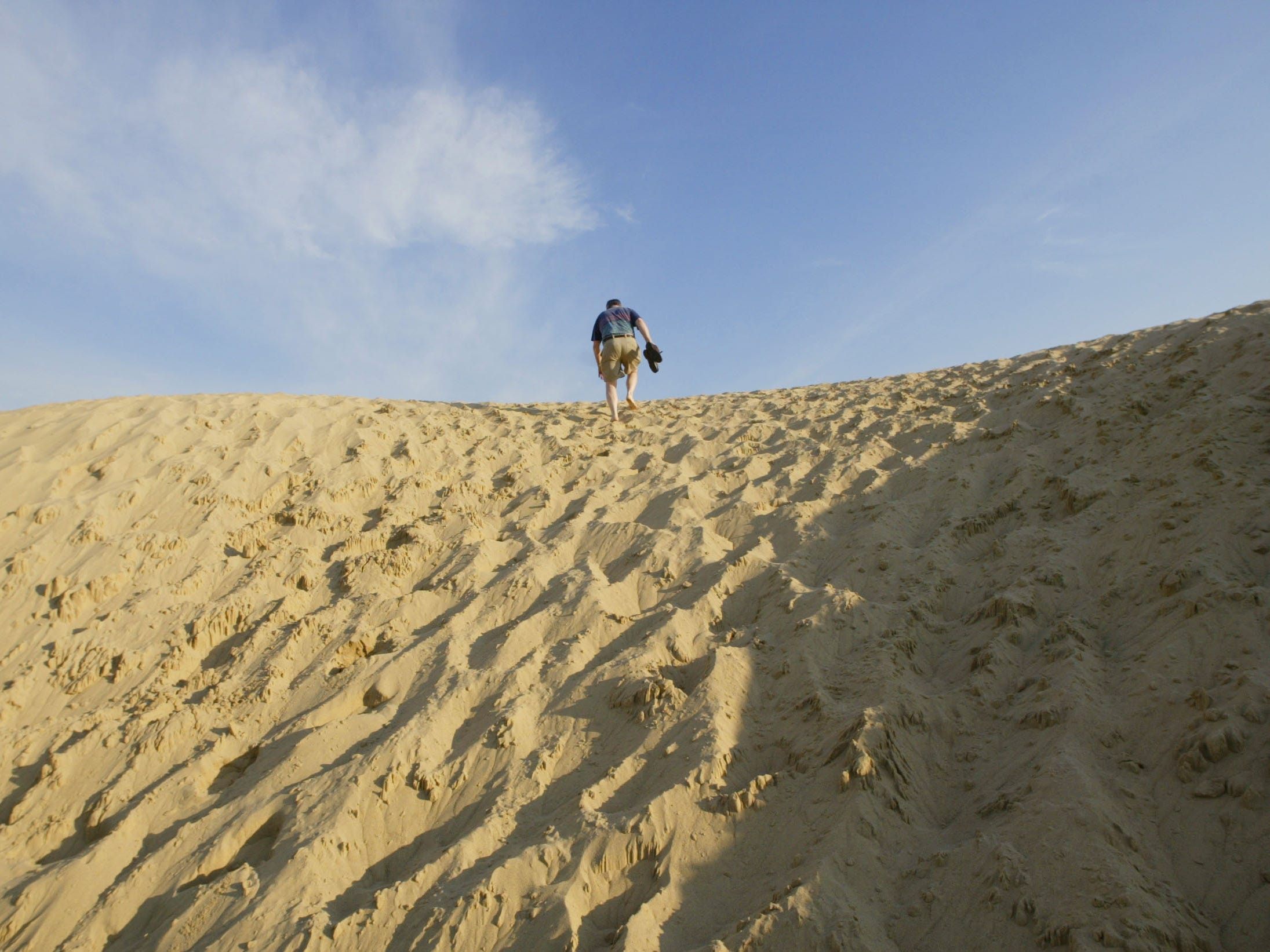 An early-morning visitor climbs to the top of Mt. Baldy at sunrise. The 125-foot-tall sand dune is the trademark of the beach near Michigan City.