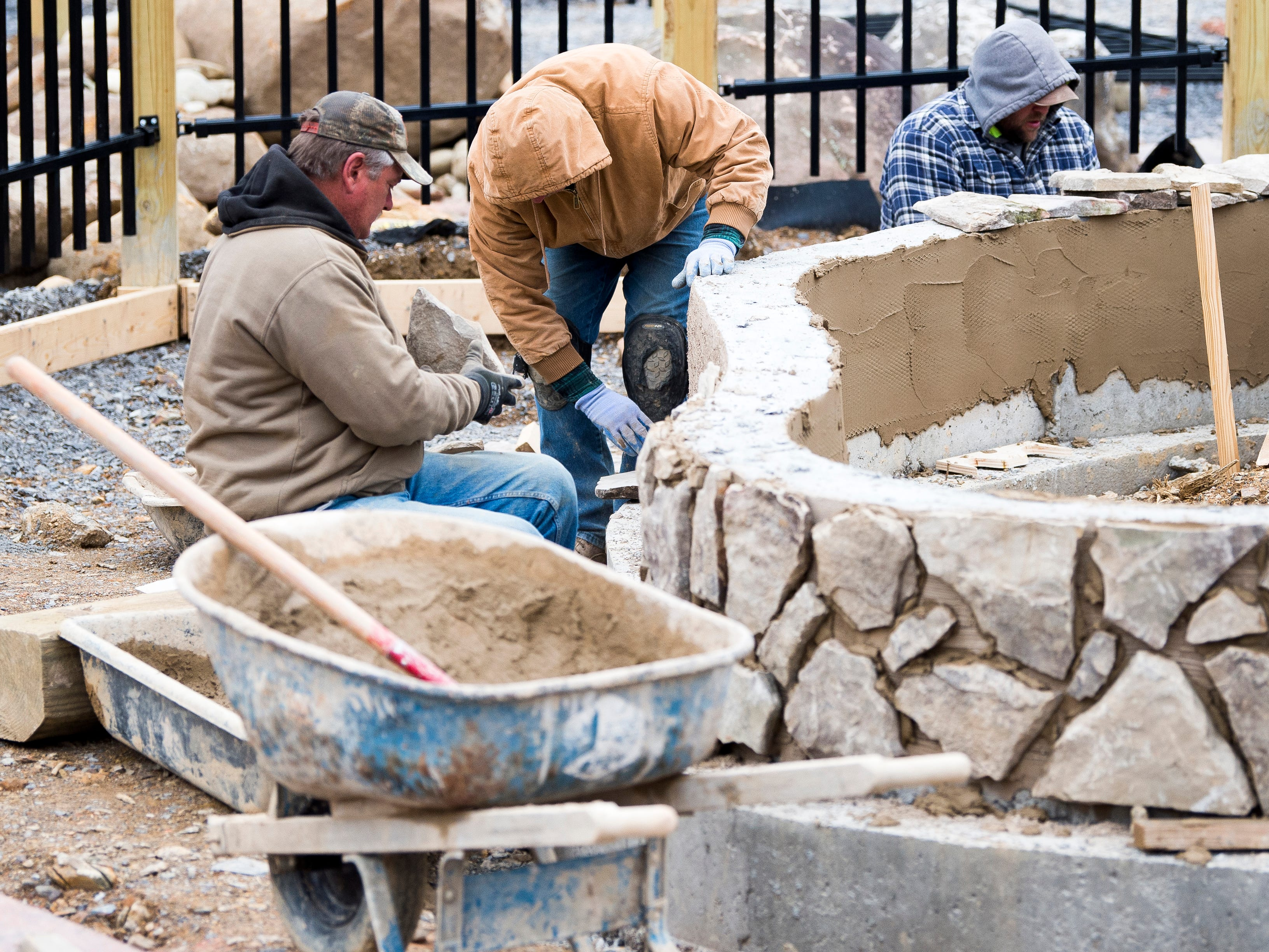 Construction workers put in rock tiles on a water feature in Dollywood's new Wildwood Grove area of the park on Tuesday, February 19, 2019.