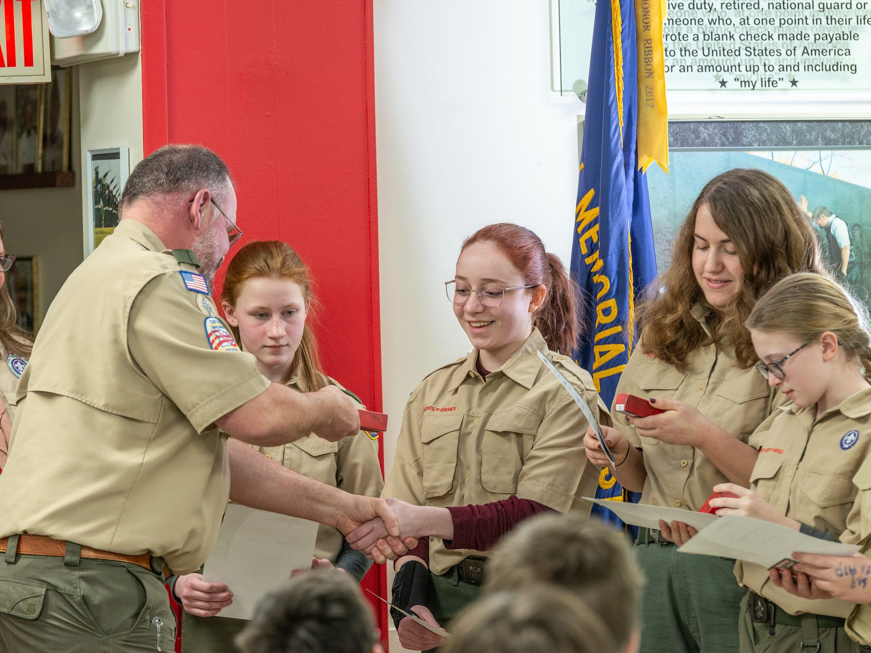Chuck Thibodeau hands Zoey Foss, 16, a welcome gift, a pocket knife, as Foss and four other girls joined Scouts BSA Monday Feb. 18, 2019.