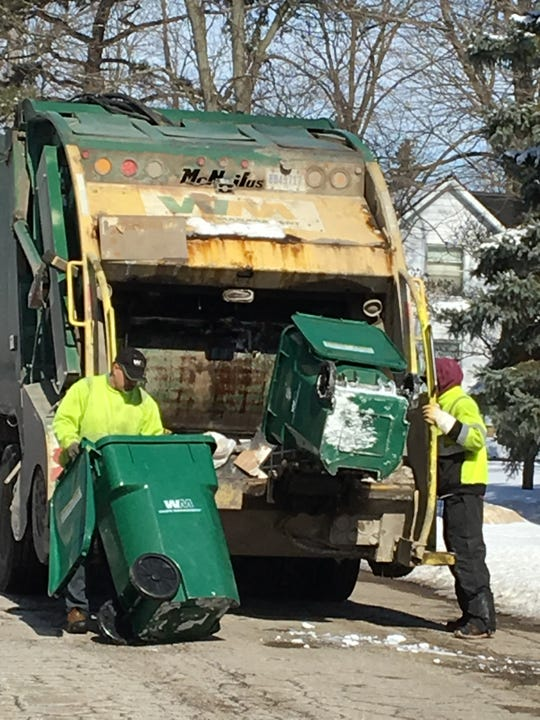 Trash being picked up Tuesday Feb. 19, 2019 by Waste Management employees at homes along North Fifth Street in Brighton. Officials say that oftentimes recyclable items are thrown away, reducing recycling opportunities.