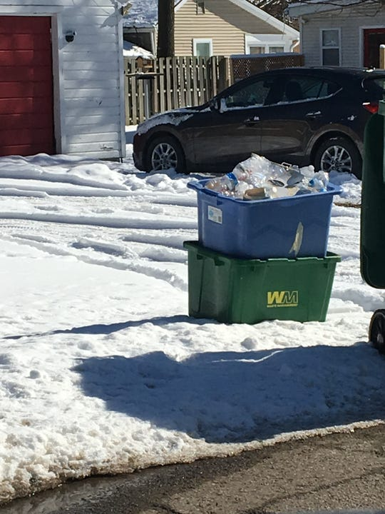 Materials to be recycled sit in a Waste Management bin on Tuesday Feb. 19, 2019 at a curb at a home in Brighton.