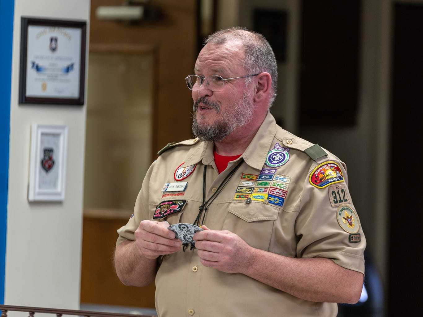 Chuck Thibodeau explains the new badges the girls will receive as Scouts on Monday Feb. 18, 2019.