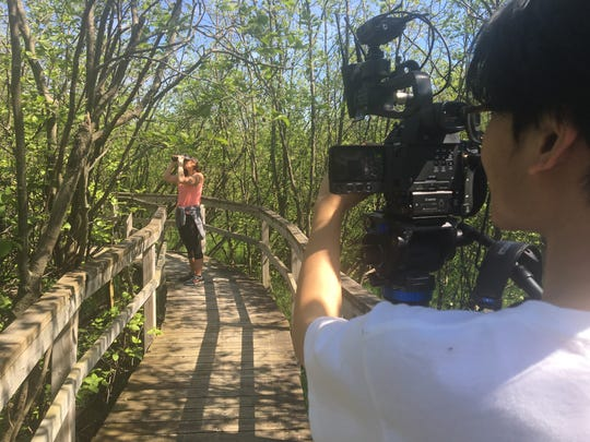 Discover Wisconsin host Mariah Haberman bird watches at Woodland Dunes as DW Crew Member Anh Vo films.
