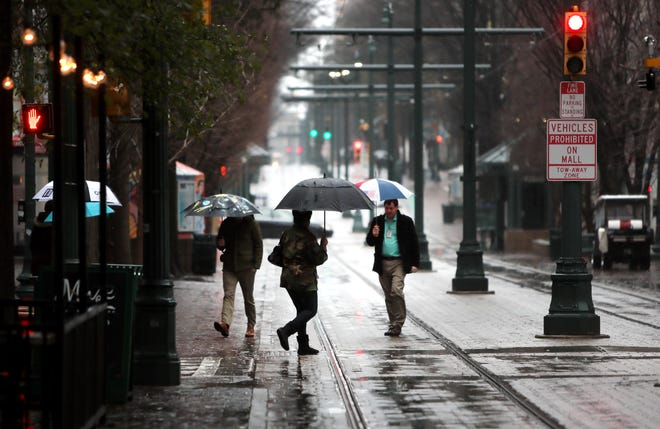 People walk across Main Street in downtown Memphis during a cold and rainy afternoon as the state prepares for a wet weather week on Tuesday, Feb. 19, 2019.