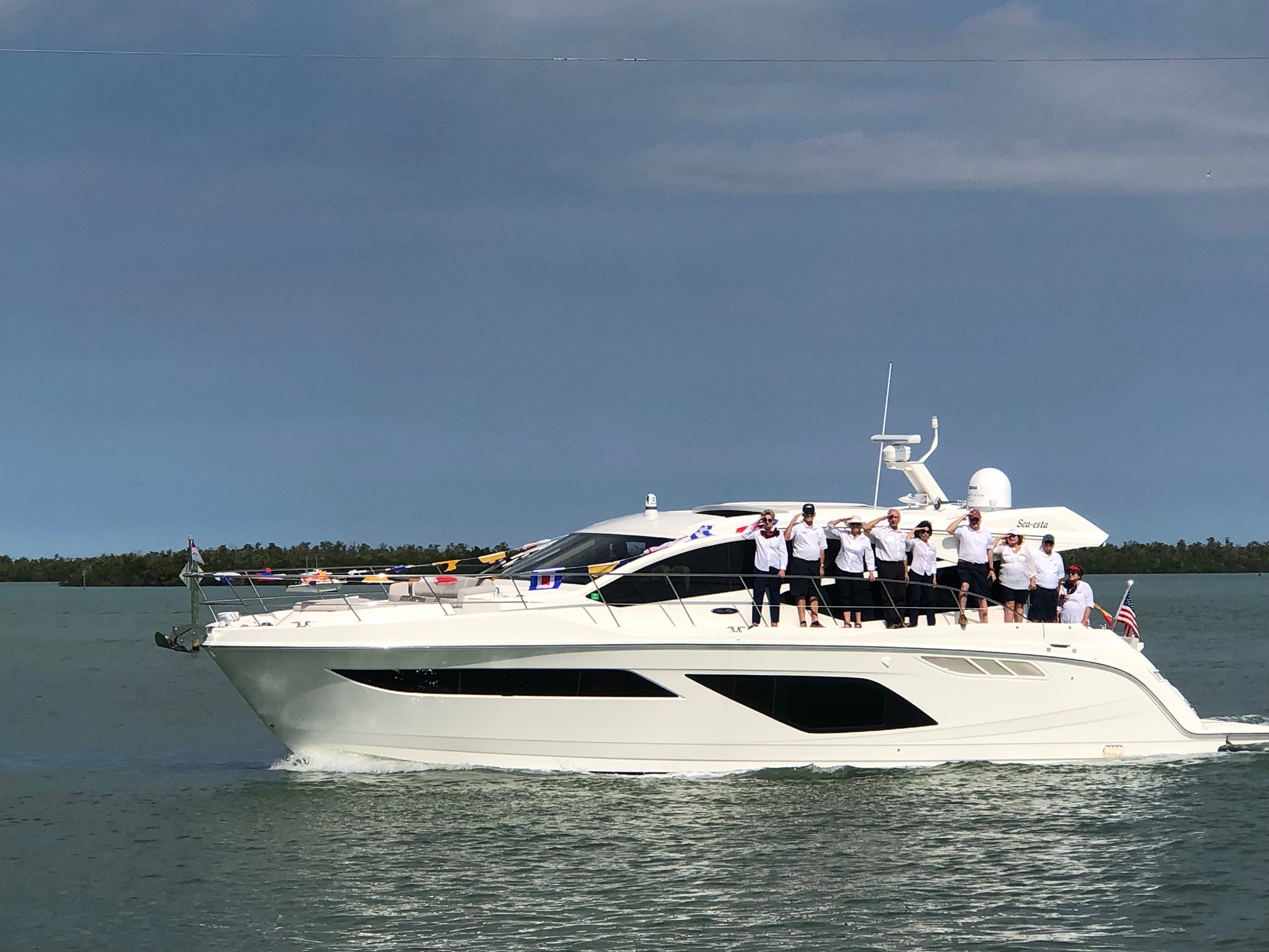 The crew of Sea-esta, owned by Dave and Ellie Everitt, salute as they pass the Marco Island Yacht Club.