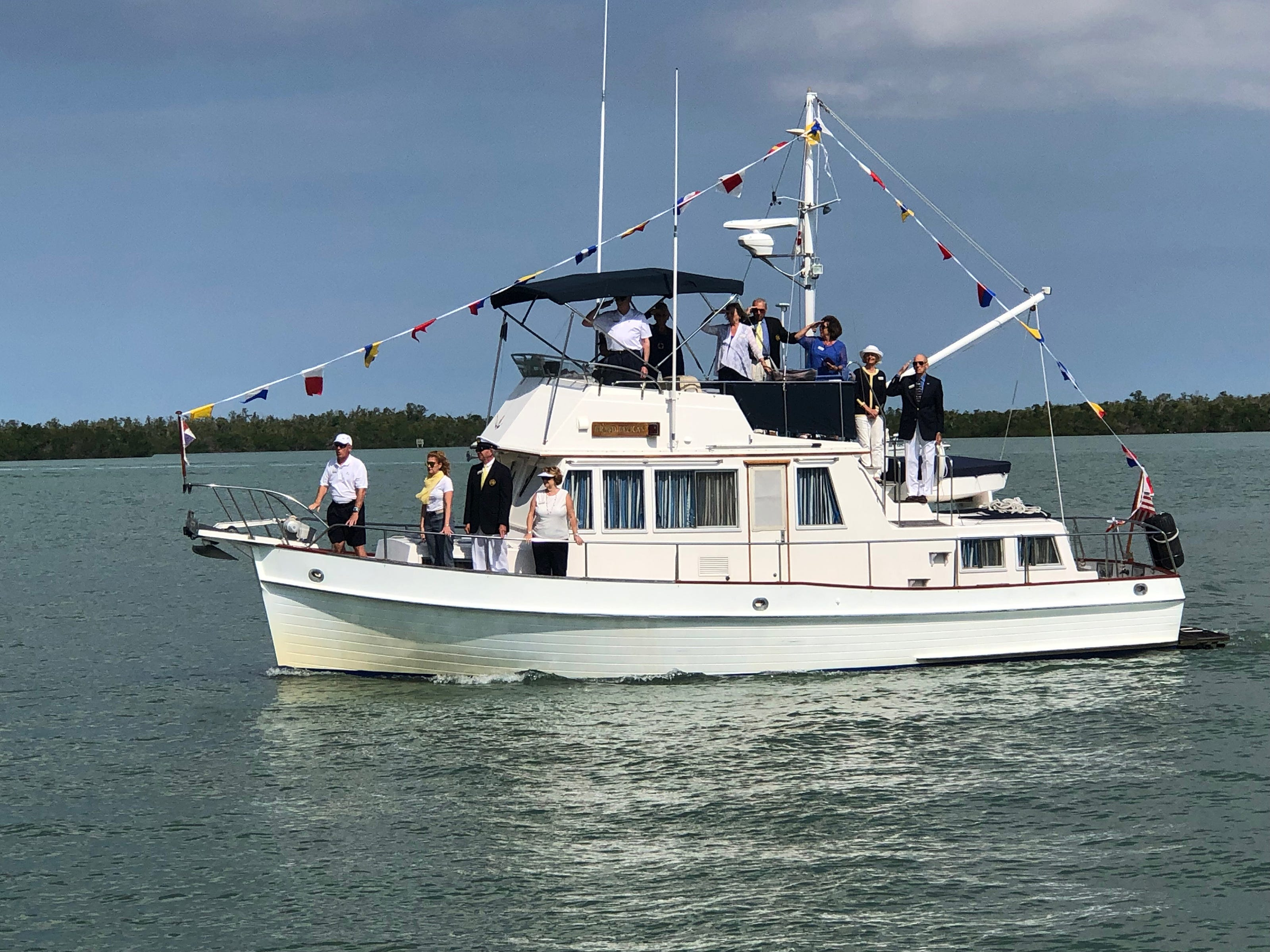 Grand Pelican Captain Pete Frazier, First Mate Peggy Frazier and crew prepare to pass the Marco Island Yacht Club and exchange salutes with MIYC bridge officers.