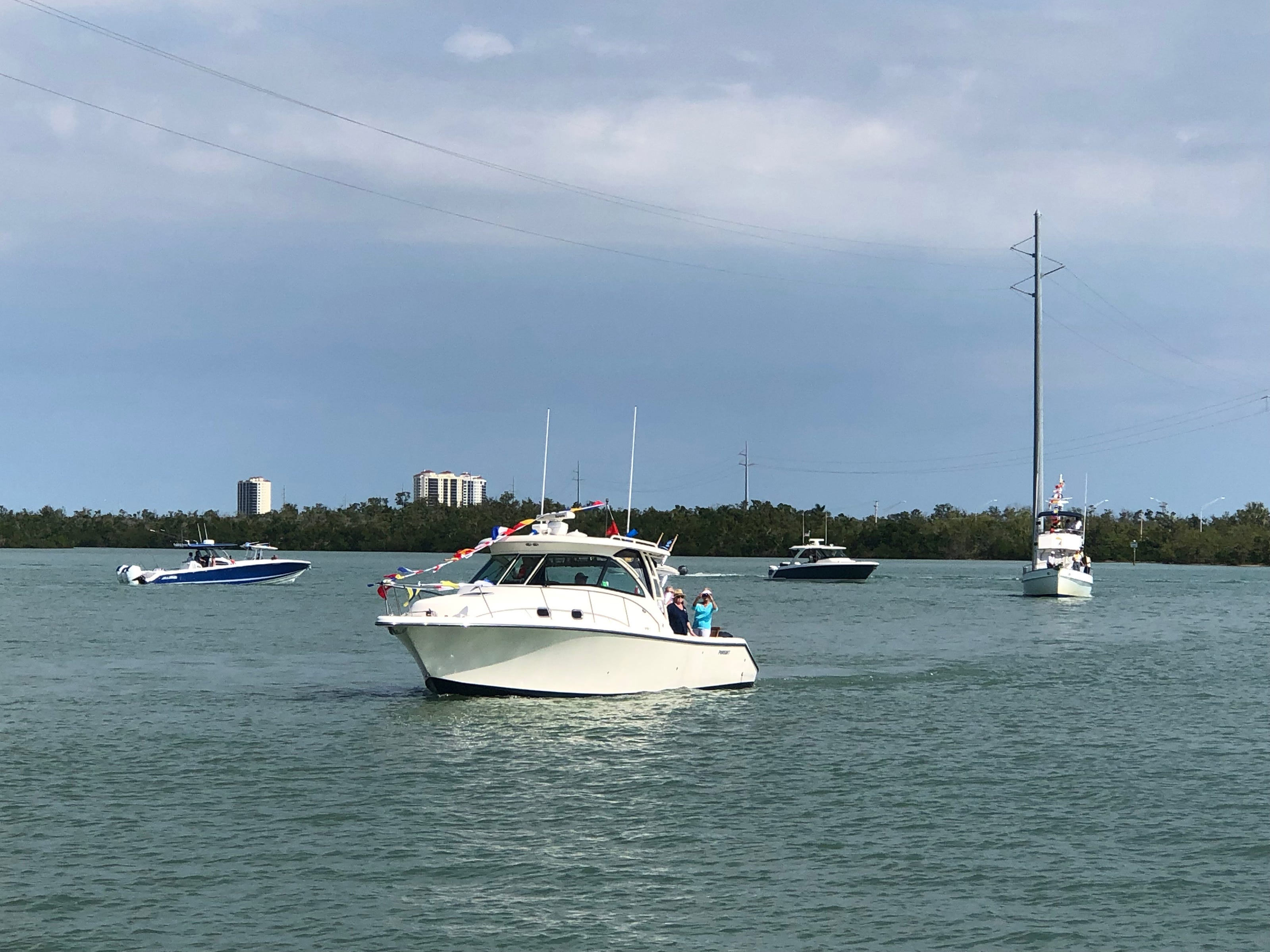 Blue Moon, owned by Jim and Linda Marr, and other fleet participants approach the Marco Island Yacht Club after receiving a maritime Blessing from Yacht Club chaplain Alan Sandlin.