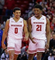D'Mitrik Trice (0) and Khalil Iverson are able to smile after the Badgers finished off Illinois on Monday night.