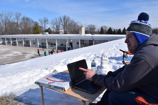 Riverside Elementary School principal Scott Walter points to his computer screen as he spends the day Feb. 19 working from the roof of his school.