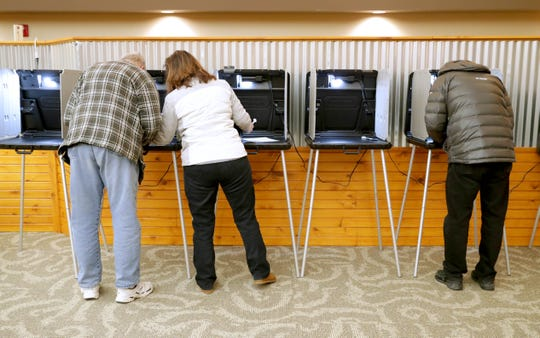 Bob Lemke, left, is assisted by his wife, Cheryl Lemke, as they vote at the Pieper Power Education Center voting location at the Mequon Nature Preserve.