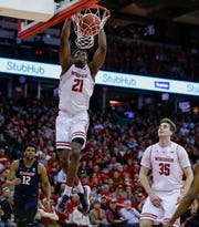 Wisconsin's Khalil Iverson (21) dunks past Illinois' Adonis De La Rosa (12) during the second half of an NCAA college basketball game Monday, Feb. 18, 2019, in Madison, Wis. Wisconsin won 64-58. At right is Wisconsin's Nate Reuvers (35). (AP Photo/Andy Manis) ORG XMIT: WIAM108