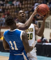 Carver's Jereme Robinson (20) is fouled by Lanier's Antwan Burnett (11) as he goes up for a layup during the Class 6A southeast regional championship at Garrett Coliseum in Montgomery, Ala., on Tuesday, Feb. 19, 2019. Carver leads Lanier 26-23 at halftime.