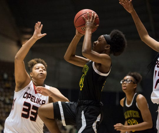 Carver's Trinity Thomas (24) goes up for a layup over Opelika's Evita Debrow (33) during the Class 6A southeast regional championship at Garrett Coliseum in Montgomery, Ala., on Tuesday, Feb. 19, 2019. Opelika leads Carver 33-22.