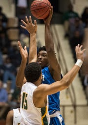 Lanier's Rongie Gordon (30) goes up for a shot over Carver's Anthony Scott (15) during the Class 6A southeast regional championship at Garrett Coliseum in Montgomery, Ala., on Tuesday, Feb. 19, 2019. Carver leads Lanier 26-23 at halftime.