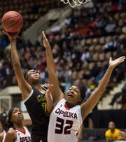 Carver's Mya Barnes (12) goes up for a layup over Opelika's Jasmine Stokes (32) during the Class 6A southeast regional championship at Garrett Coliseum in Montgomery, Ala., on Tuesday, Feb. 19, 2019. Opelika defeated Carver 61-54.