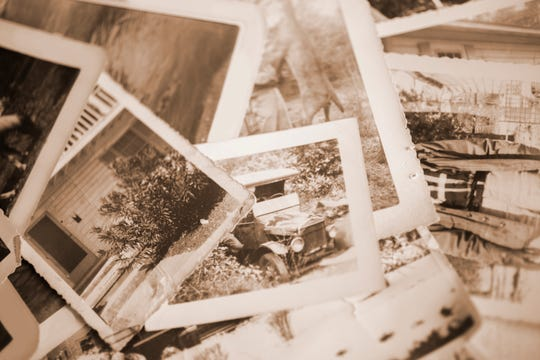 Many vintage, sepia-toned photographs from the 1940s lying in a large pile.