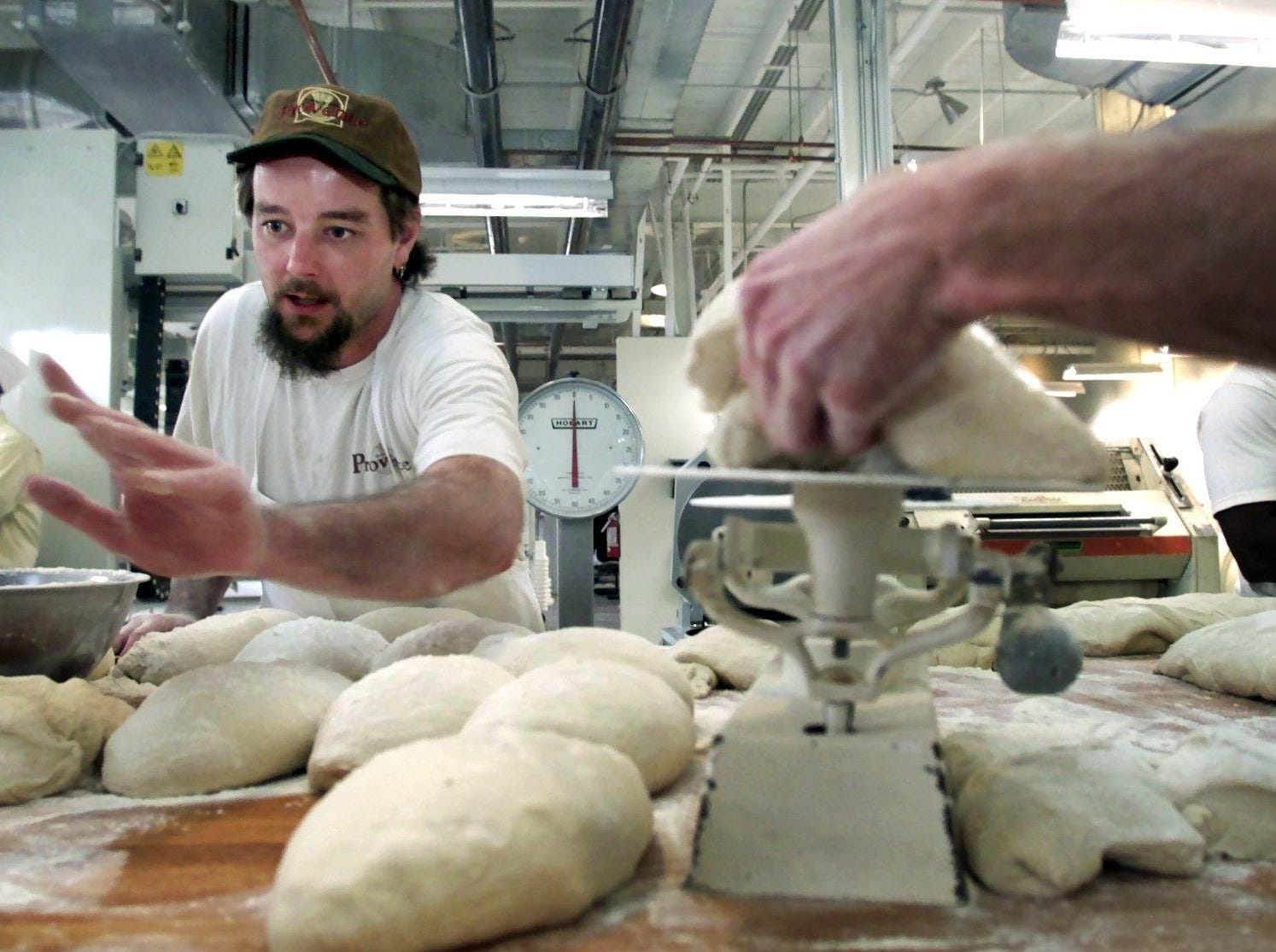 Dallas Mayberry counts loaves of Tuscan bread as the bread makers shape the dough at the new Provence wholesale site on 12th Avenue South Dec. 11, 2001.