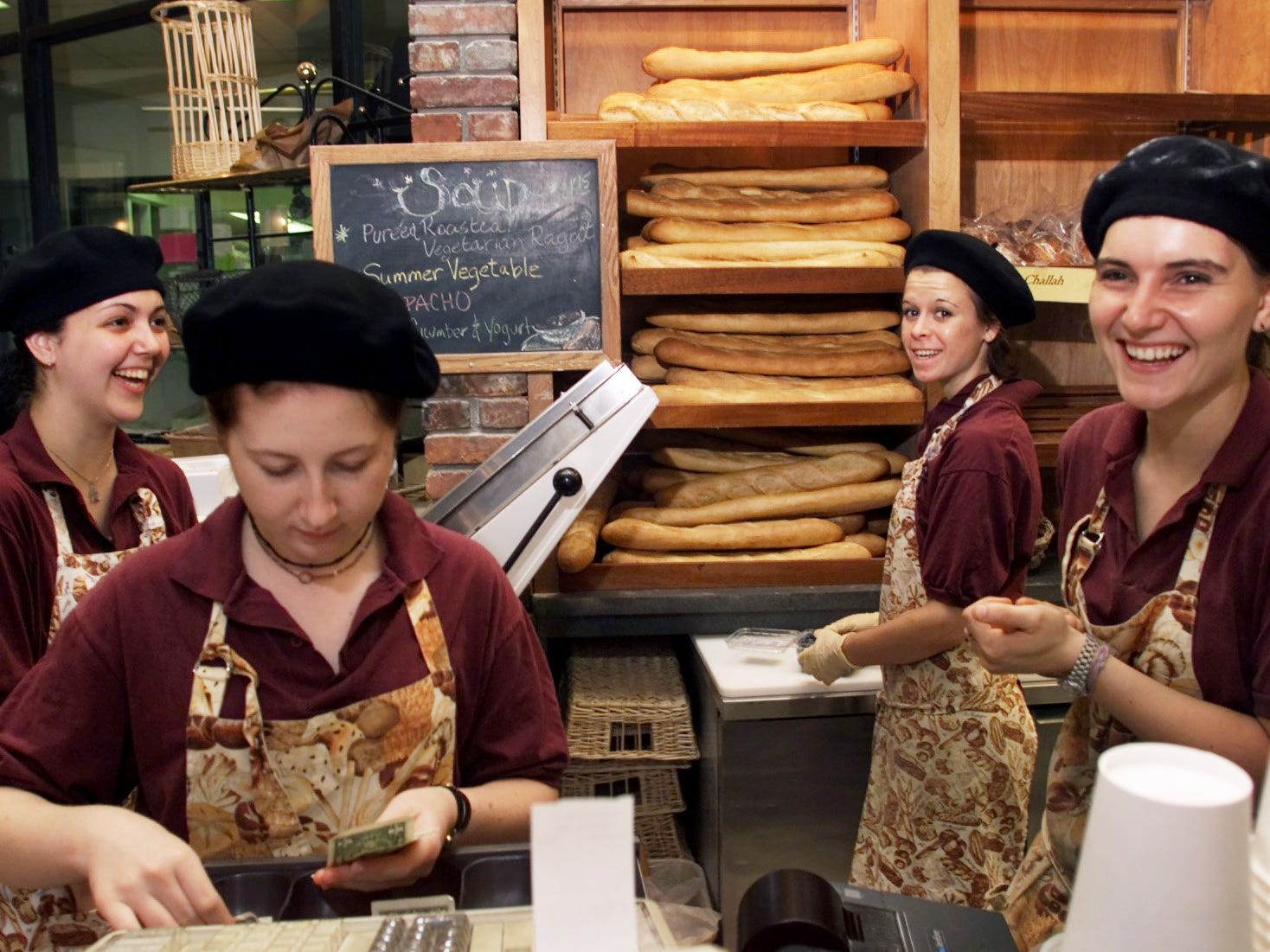 The addition of French berets for Bastille Day in the Village, along with their French aprons, Devon Hedgecoth, left, Kelda Olson, Jessica Limbird and Whitney May help serve customers at Provence Breads and Cafe July 14, 2000.