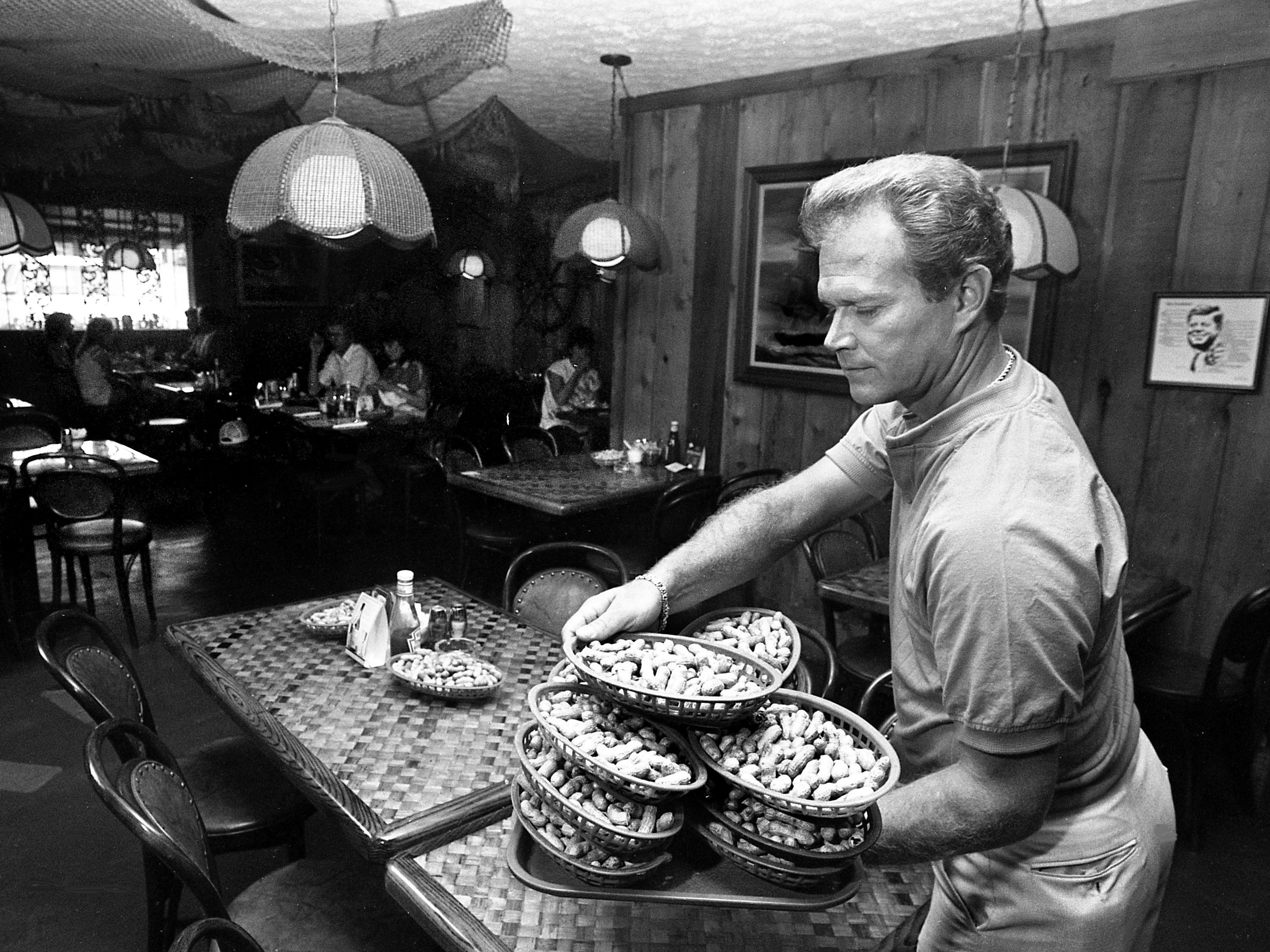 Bill Carmen, owner of The Shack Seafood Restaurant, is getting ready to welcomes patrons June 9, 1987 with a complimentary bowl of peanuts - and isn't at all distressed when the floor is littered with shells. The Shack, in a building reminiscent of coastal seafood shanties, is about two miles north of Rivergate Mall and has been serving the area for 13 years.