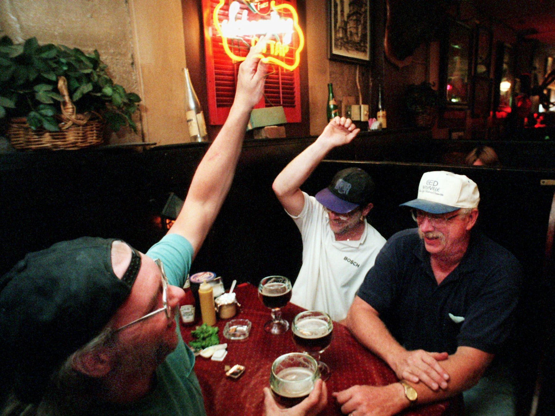 Benny Still, left, and Drew Denton high five as they enjoy beers with Keith Vaughn at the Gerst Haus Restaurant Aug. 27, 1998. Vaughn has been going to the Gerst Haus since it opened at the present local. The Gerst House will closed those doors for good Aug. 29 because of the football stadium.