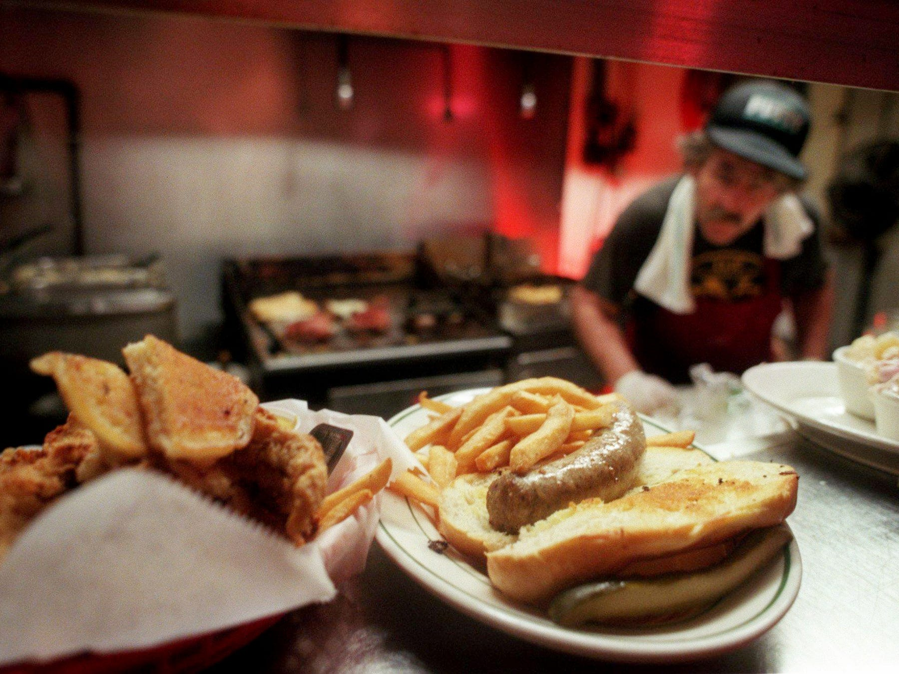 A bratwurst sandwich, center, and other German cuisine awaits diners as kitchen manager Don Scott cooks up more orders during lunch at the Gerst Haus Restaurant  Aug. 14, 1998. The Nashville landmark is moving due to the building of the football stadium.