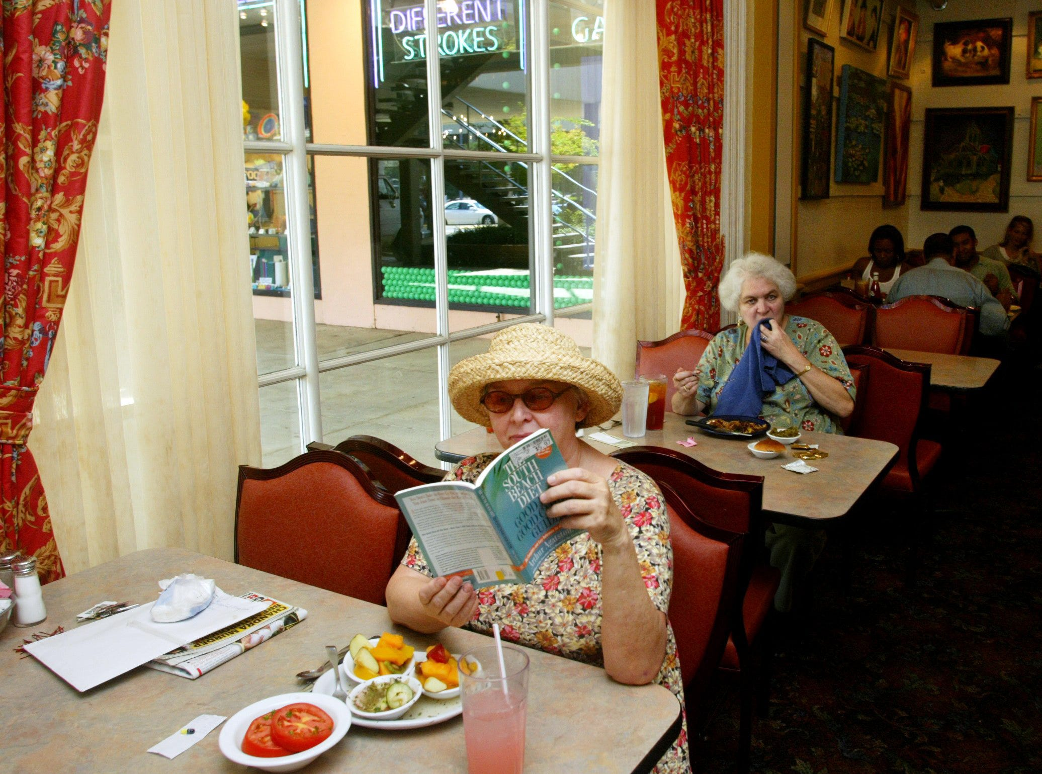 """Kelly Mattox, left, of Nashville reads """"The South Beach Diet"""" while dining at the Belle Meade Cafeteria Sept. 14, 2004. Mattox eats at the restaurant on Harding Pike once a week."""