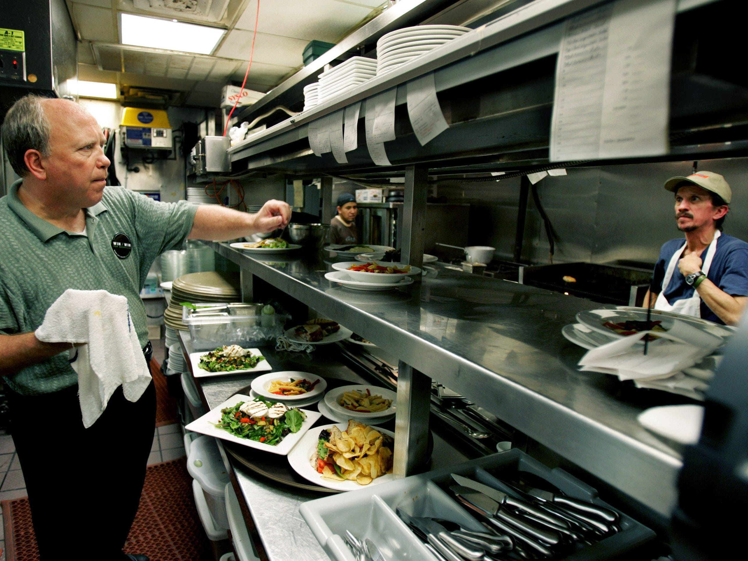 Randy Rayburn, left, owner of Sunset Grill in Hillsboro Village, set up the orders in the kitchen Oct. 17, 2006 during the lunch crowd. Cookers are Al Rubio, center, and Randy McClendon.