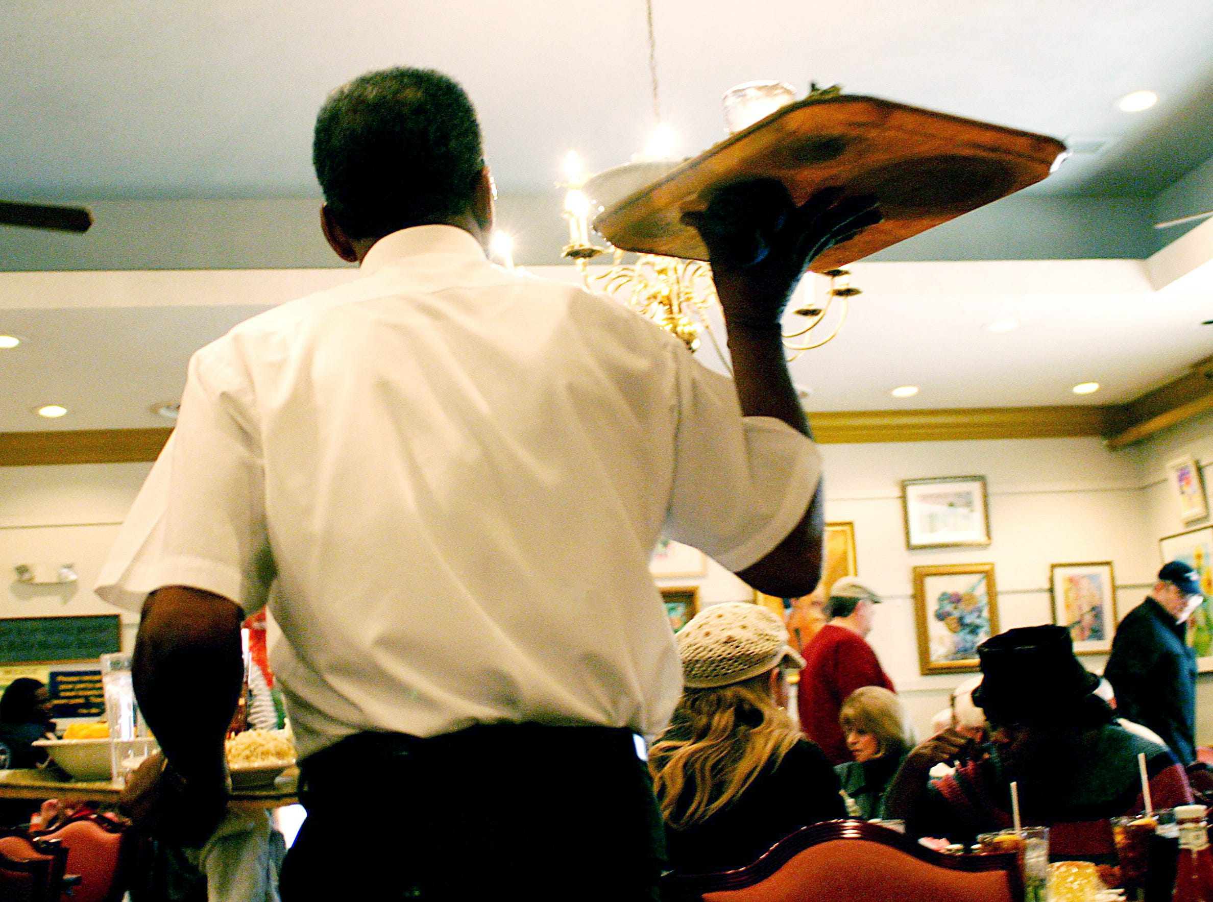 Bobby Spurlock, a waiter at The Belle Meade Cafeteria carries a tray to a guest as the lunch time crowd fills the room Dec. 31, 2003.