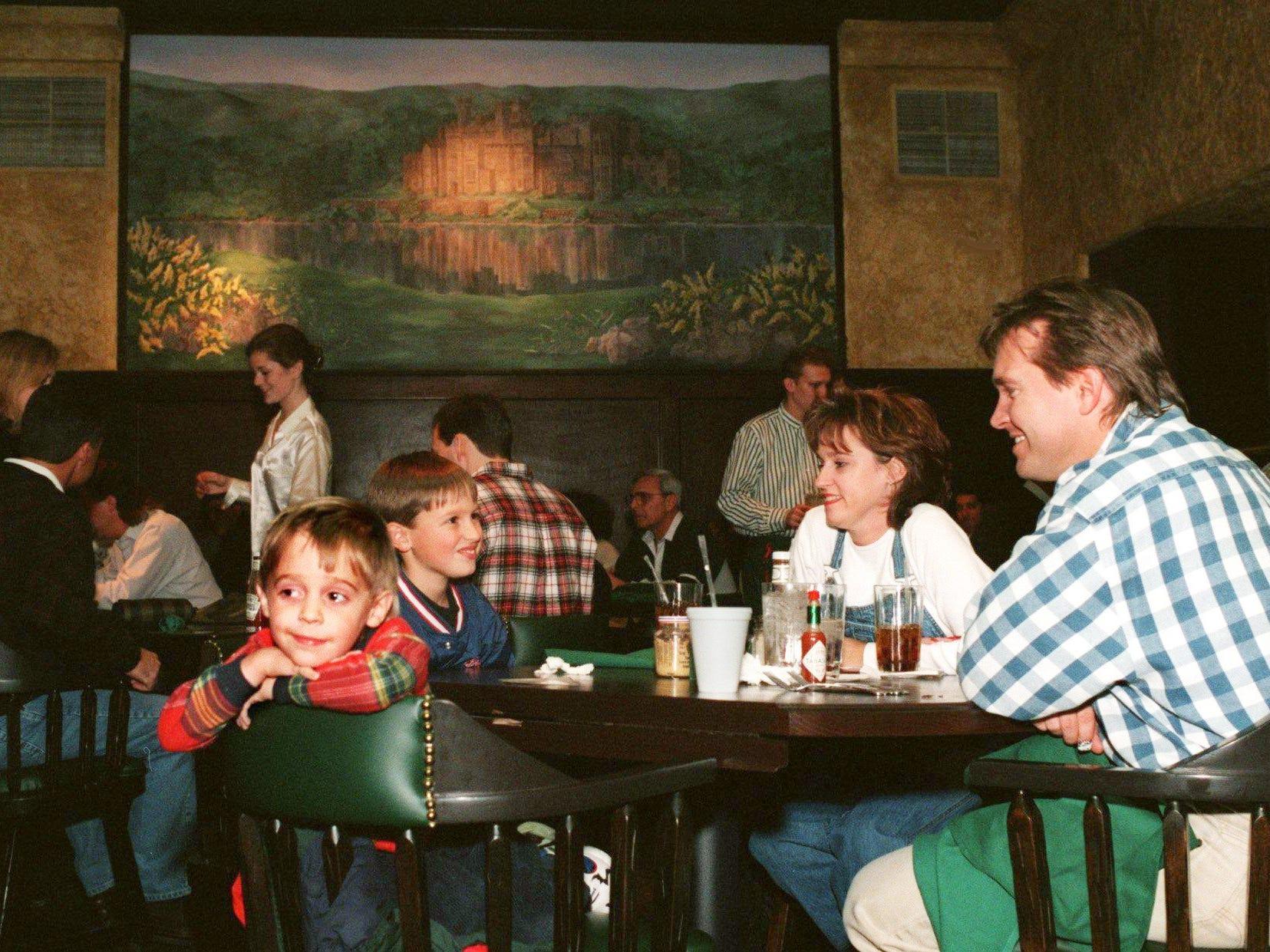 Austin Casassa, left, Ryan Casassa, Julie Casassa and Curt Casassa wait for their food at Ireland's Nov. 23, 1997.