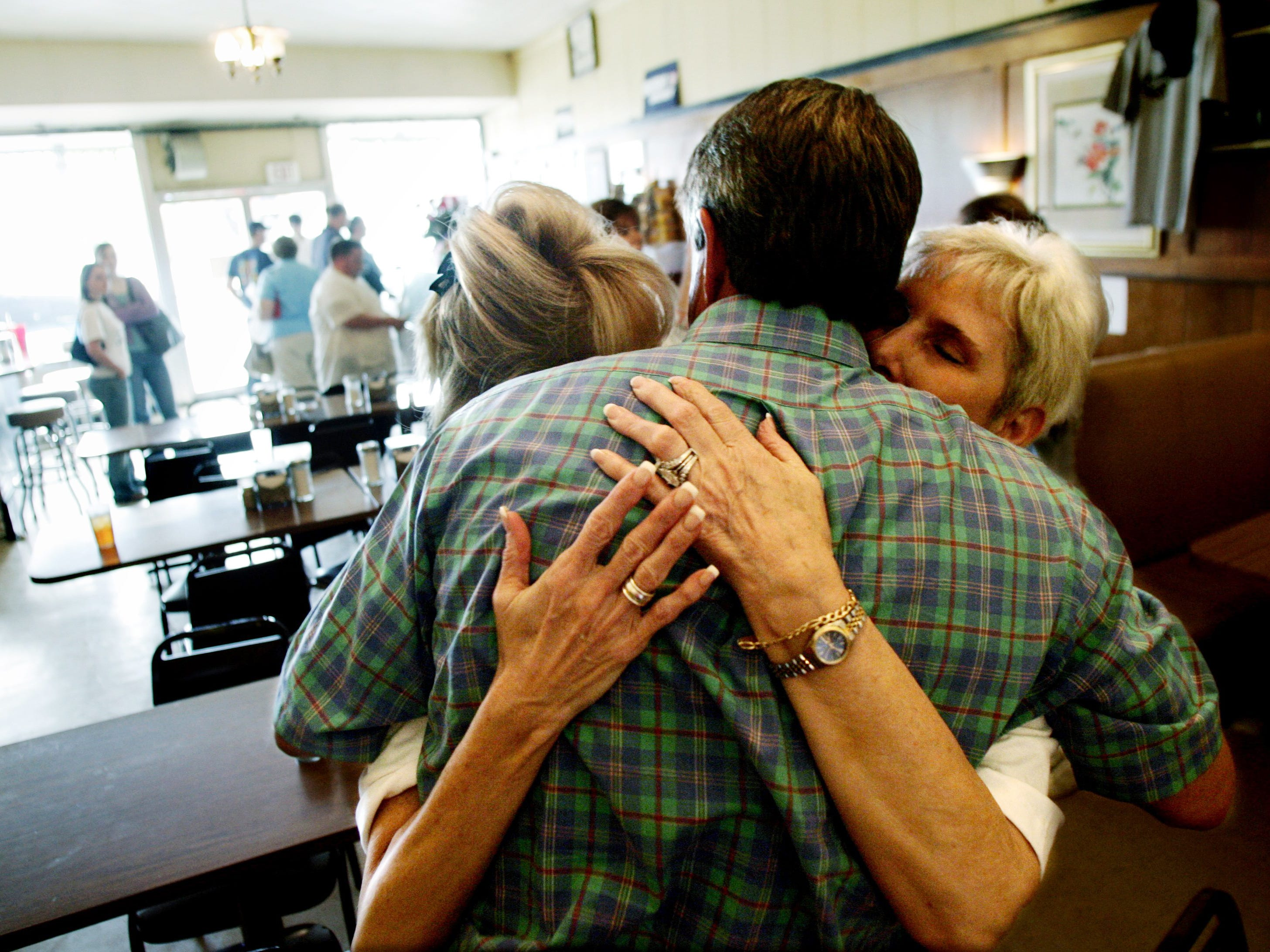 Long time customer Ham Wallace gets a hug from waitress Malinda Abell, left, and owner Bea Givens in the final minutes that Vandyland was open May 19, 2006.
