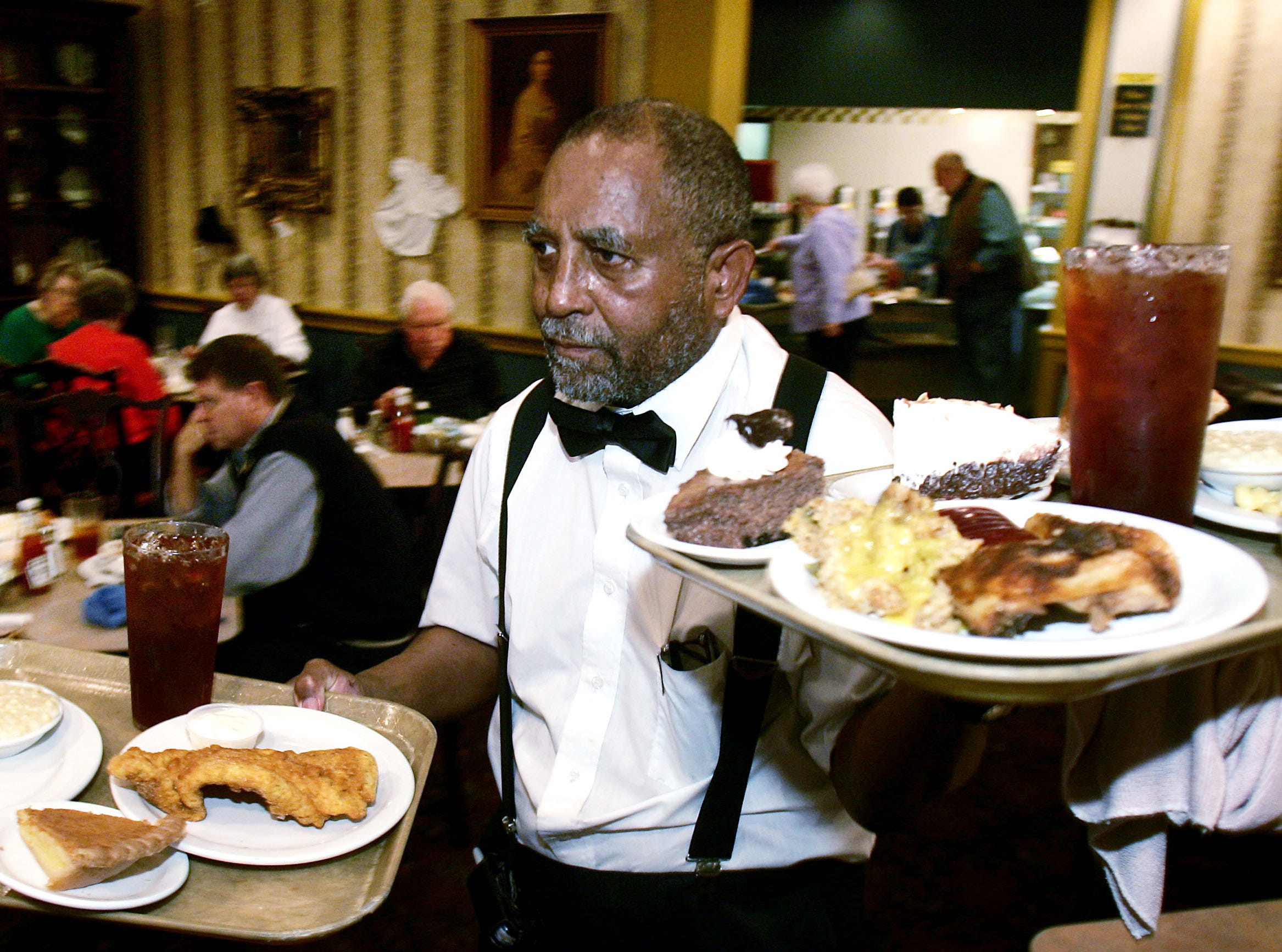 """Gus McGlasken has been working at the Belle Meade Cafeteria """"for some 25 plus years now,"""" he says as he carries food to his tables Dec. 21, 2006. Owner Corey Nix said he expects about 40 jobs to be lost when the restaurant closes."""
