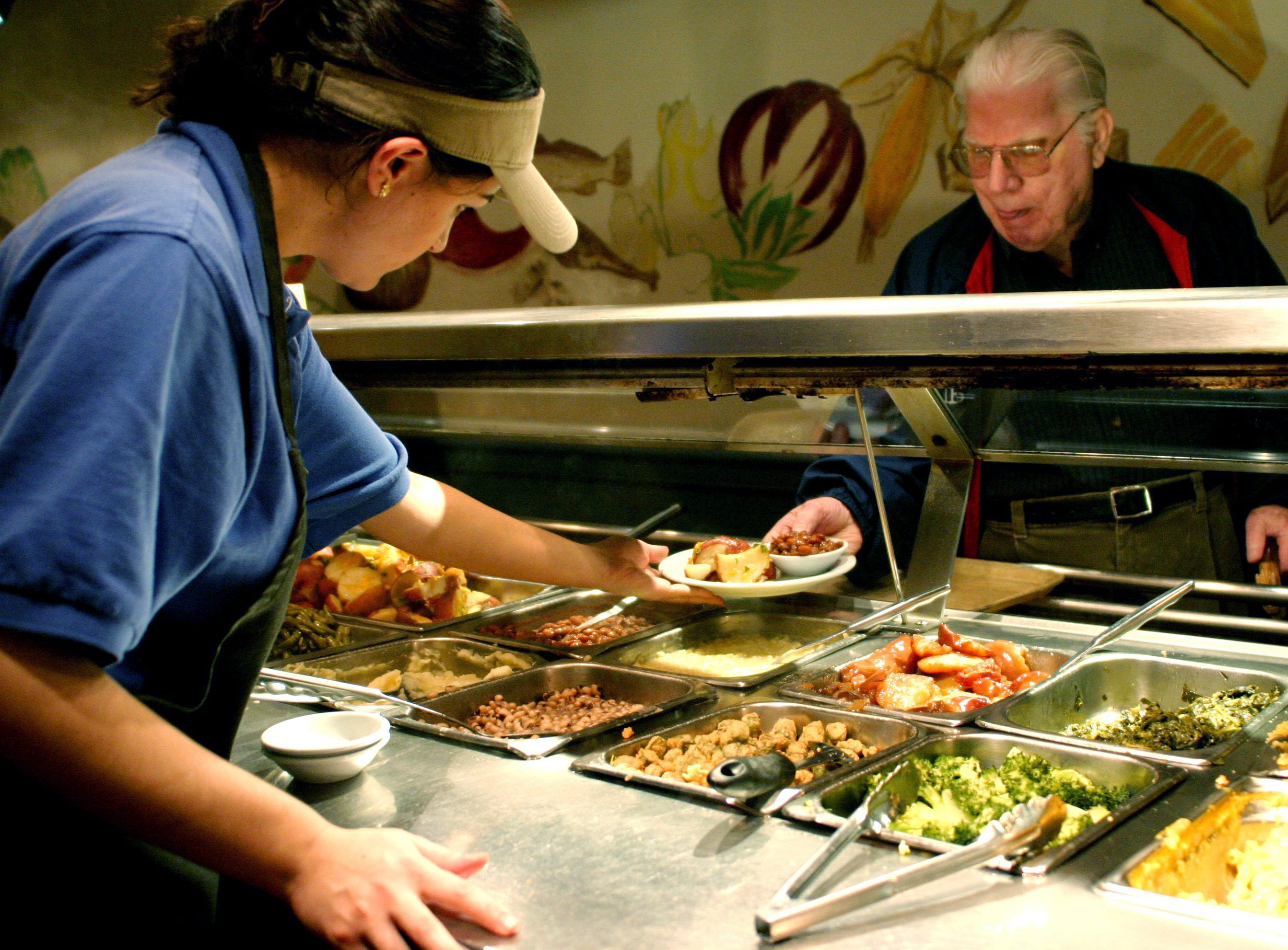 Clay Coble, right, a retired educator makes his way through the line at the Belle Meade Cafeteria as Bukurie Zymeri hands him his plate Dec. 31, 2003. The cafeteria is the city's oldest free standing restaurant and maintains it old charm and classic taste.