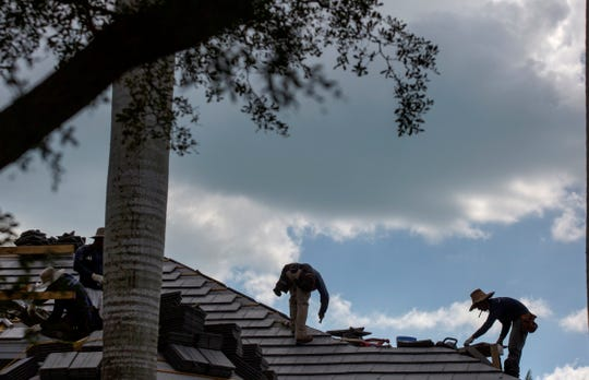 Roofers work on a home Tuesday, Feb. 19, 2019, along Crayton Road in Naples.