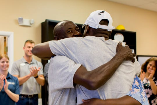 Mackensie Alexander (white hat) hugs his parents, Jean and Marie, after paying off their Habitat for Humanity home at the Collier County chapter's office in Naples. Alexander is a cornerback for the NFL's Minnesota Vikings and a graduate of Immokalee High School.
