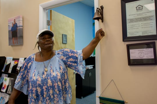 Marie Alexander rings the bell at the Habitat for Humanity of Collier County office in Naples on Friday, signifying the mortgage on her Habitat home has been paid off. Alexander's son, NFL player and Immokalee native Mackensie Alexander, paid off the mortgage at a small ceremony.