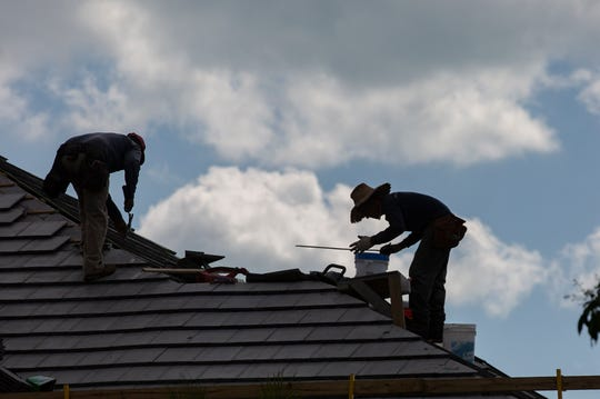 Roof work continues on a home  Tuesday, Feb. 19, 2019, on Crayton Road in Naples.