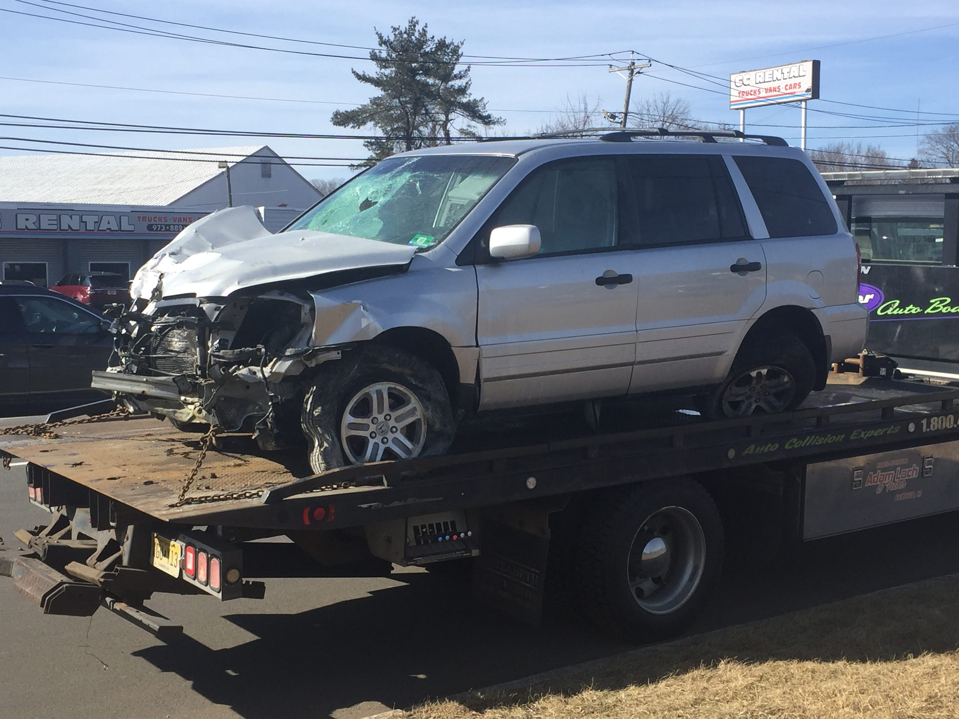 Police towed the car of the driver suspected of killed three people in a crash in Wayne.